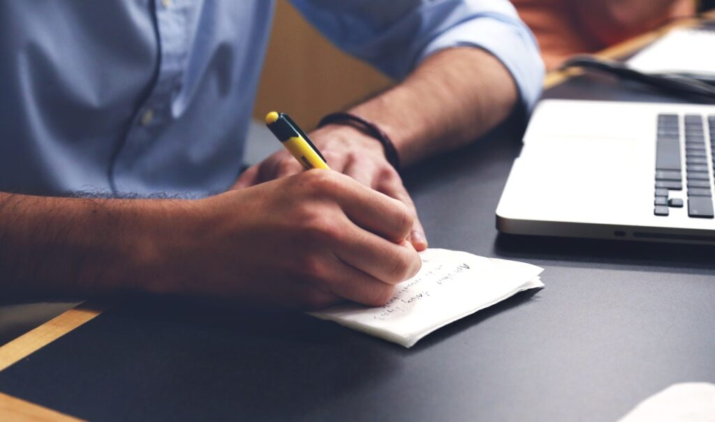 man's hand writing resume action words on a piece of paper