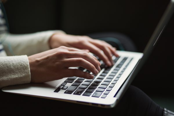 hands typing resume objective on laptop