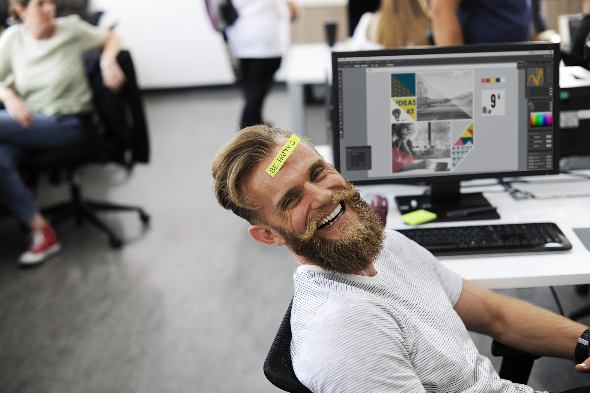 Pros in Working at FAcebook: Perks and Benefits makes a man with a sticky note on his forehead  laugh in front of his laptop