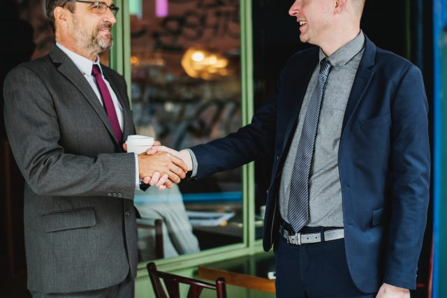 an employer shakes hands with his applicant after a successful salary negotiation