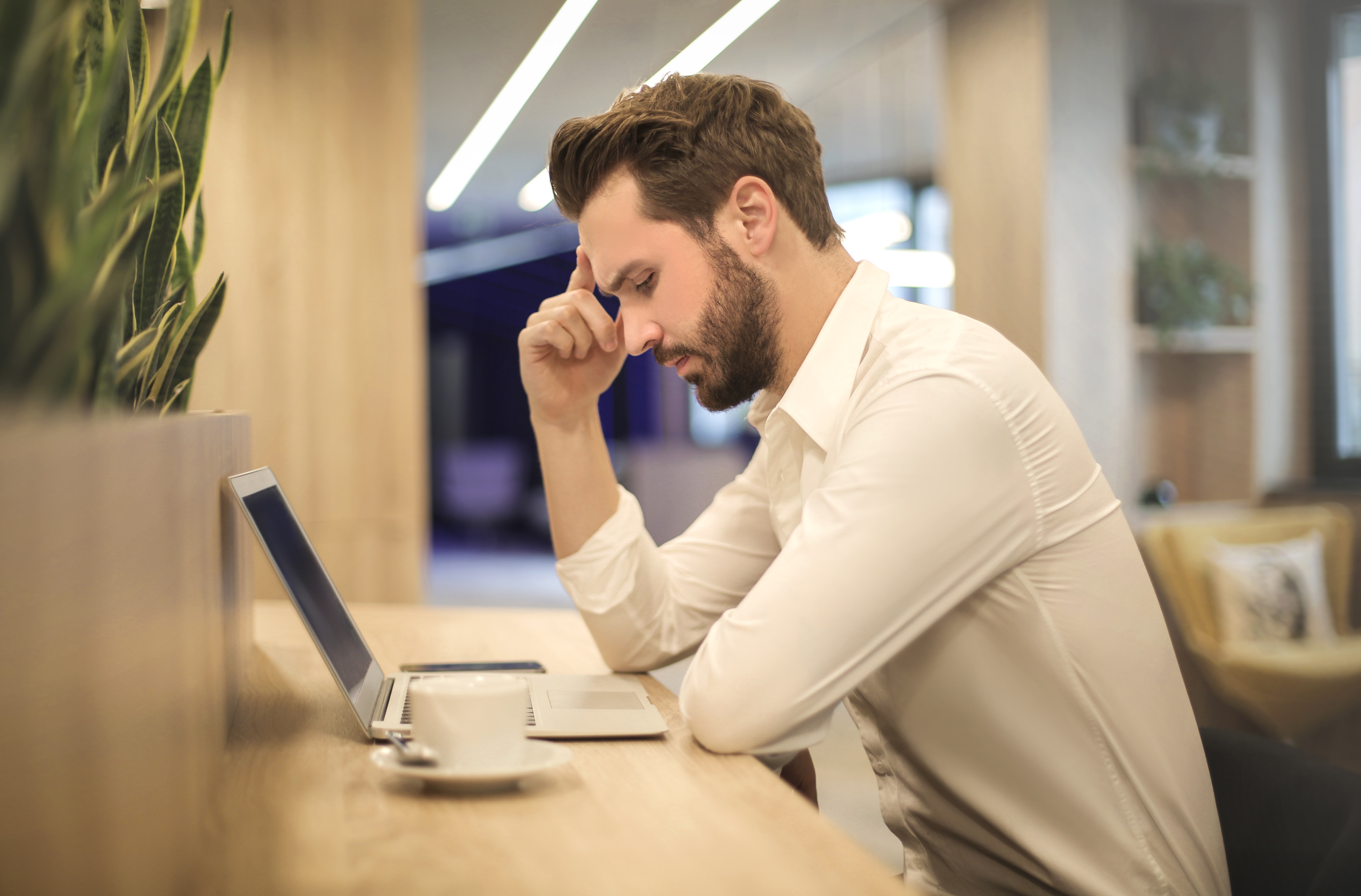 Current Job Consideration Man thinking of plans in front of laptop
