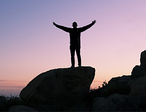man on hilltop celebrating career success