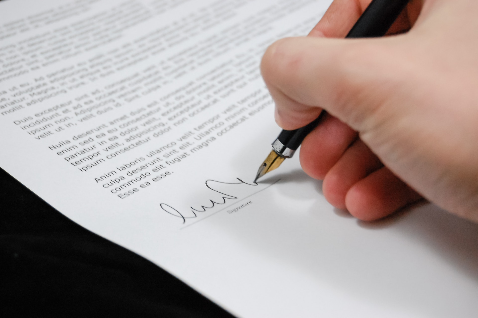 A person affixes his signature on a cover letter