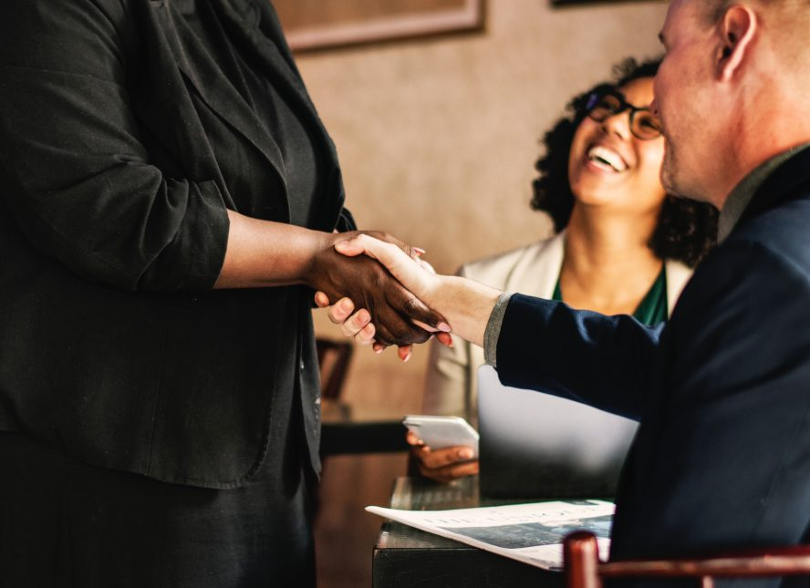 a woman and her boss shaking hands because of the job promotion given to her